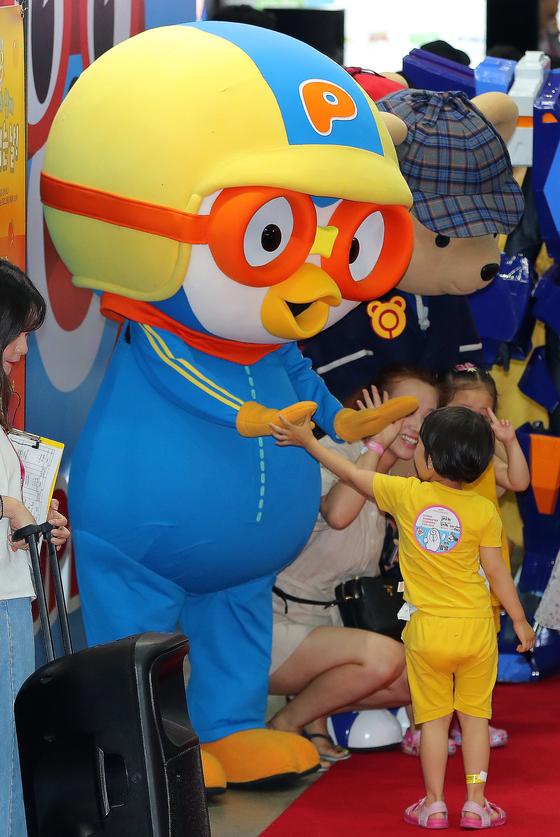 7월 17일 서울 강남구 코엑스에서 열린 제23회 서울국제만화애니메이션 페스티벌(SICAF)를 찾은 아이가 인기 캐릭터 '뽀로로'와 하이파이브 하고 있다. [뉴스1]