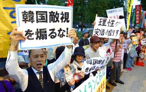 19일 오후 도쿄 나가다초 국회의사당 주변에서 열린 '일한(한일)시민 연대하자' 집회에서 한 참가자가 '한국 적대시를 부추기지 말라'는 손팻말을 든 채 구호를 외치고 있다. [연합뉴스]