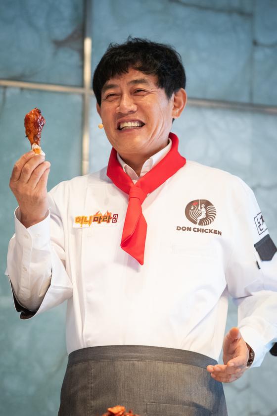방송인 이경규가 20일 서울 중구 플라자호텔에서 열린 신메뉴 '이경규 치킨' 발표 기자간담회에서 '허니마라치킨'을 소개한 후 맛보고 있다. [뉴스1]