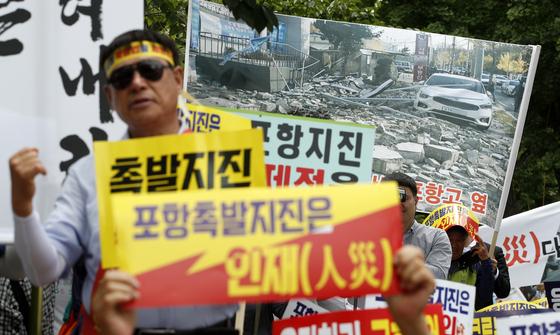 지난 6월 서울 여의도 국민은행 앞에서 열린 11·15지진 포항범시민대책위원회 '포항지진피해특별법 제정 촉구 집회'에서 포항 시민들이 구호를 외치고 있다. [뉴스1]