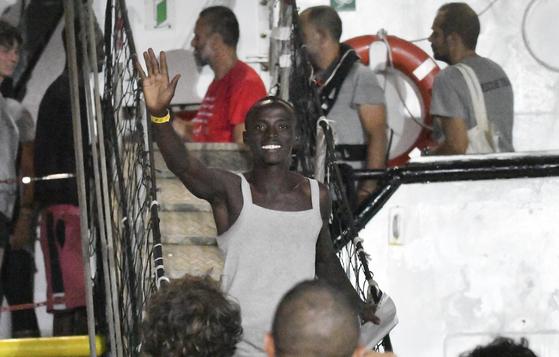 해상에 머물던 스페인 구조선이 이탈리아 항구로 입항하자 한 난민이 손을 들어보이고 있다. [AP=연합뉴스]