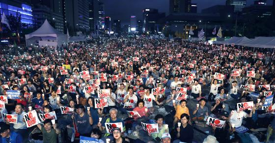 지난 15일 오후 서울 광화문광장에서 열린 '8·15 아베 규탄 범국민 촛불문화제'에 참석한 시민들이 손피켓과 촛불을 들고 일본 아베 정권의 역사 왜곡과 경제 보복 조치를 규탄하고 있다. 최승식 기자