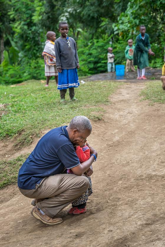 탄자니아 아루샤 지역 한 마을 어귀에서 난생 처음 본 동양인들의 모습에 놀라 울음을 터뜨린 꼬마를 안아주는 탄자니아 컴패션 직원의 모습. 비전트립 일행을 인솔하던 중 걸음을 멈추고 그 자리에 앉아 아이를 꼭 끌어안은 모습이 인상적이다. [사진 한국컴패션]