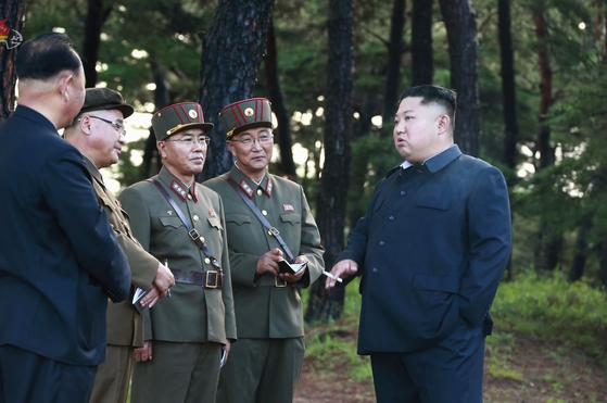 조선중앙TV가 16일 공개한 미사일 발사 현장으로 김정은 국무위원장이 수행원들과 대화하고 있다. [연합뉴스]