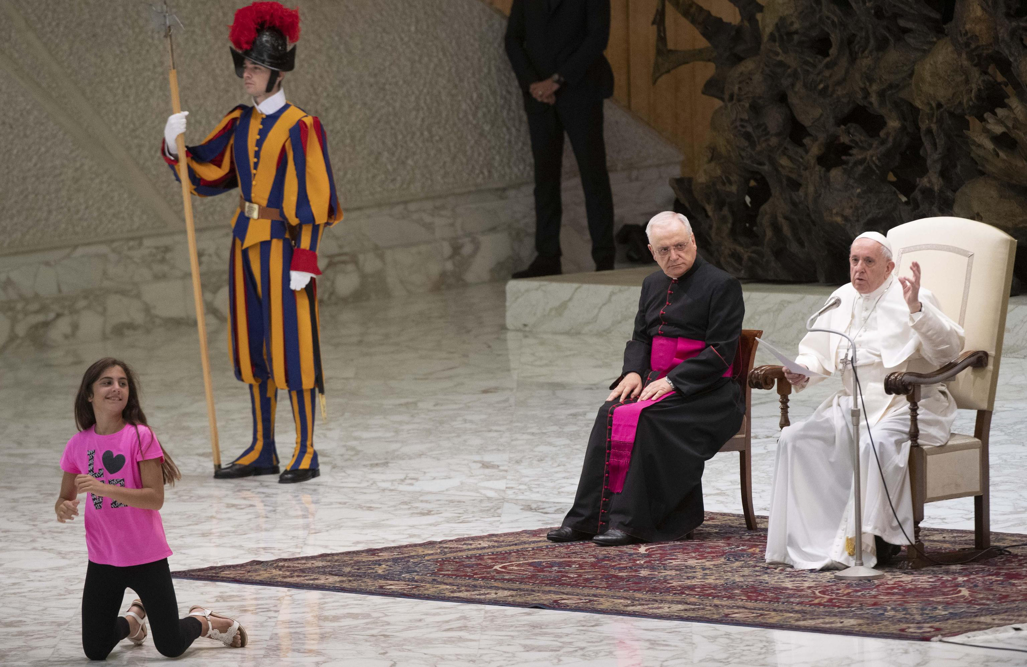 21일(현지시간) 바티칸에서 열린 일반알현에서 어린 소녀가 연단에 올라와 프란치스코 교황이 설교를 하는 동안 놀고 있다. [EPA=연합뉴스]