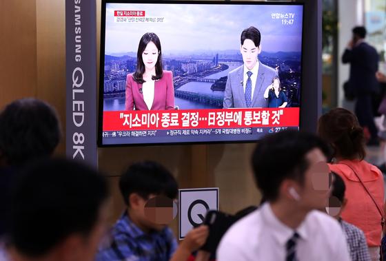 청와대가 '한일군사정보보호협정'(GSOMIA·지소미아)를 연장하지 않기로 밝힌 22일 오후 서울역에서 시민들이 관련 뉴스를 보고 있다. [연합뉴스]