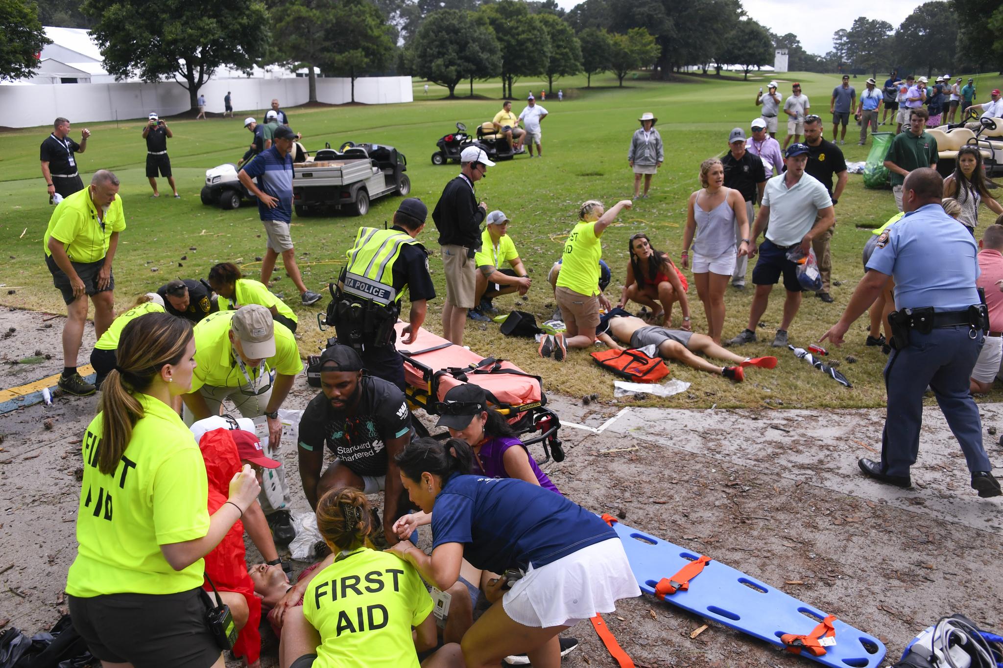 24일(현지시간) 오후 미국 조지아주 애틀랜타 이스트 레이크 골프클럽에서 구조대원들이 쓰러진 갤러리들을 응급처치하고 있다. [AP=연합뉴스]