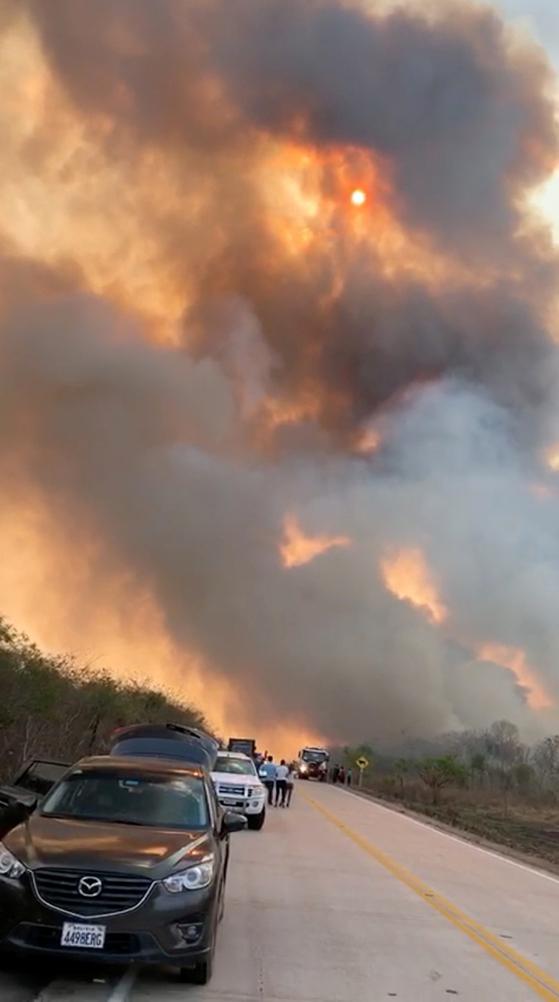 24일 볼리비아 산타 크루즈의 Aguas Calientes에서 대형 산불이 발생해 연기가 하늘을 덮고 있다. [로이터=연합뉴스]