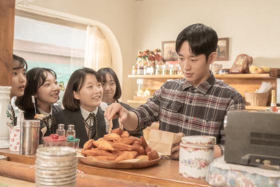 영화 '유열의 음악앨범'의 1994년 장면. 현우(정해인)가 알바로 일하게 된 미수(김고은)네 빵집에 학생들이 몰려온다. 현우는 미수와 11년에 걸친 엇갈린 만남을 이어간다. [사진 CGV아트하우스]