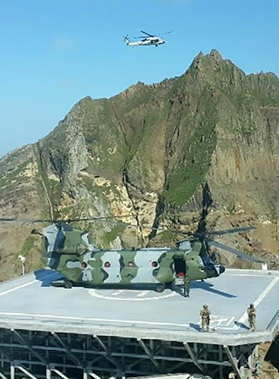 동해 영토수호훈련을 시작한 25일 대형수송헬기치누크(CH-47)로 독도에 상륙한 해군 특수부대원들과 해병대원들이 사주경계를 하고 있다. [뉴스1]