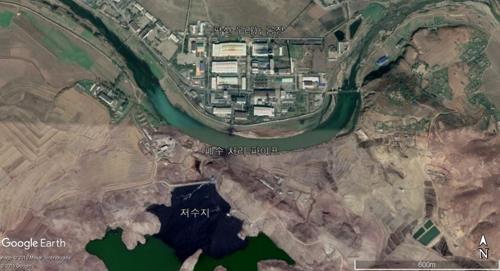 위성사진에 포착된 북한의 평산 우라늄 공장. 저수지가 공장에서 방출된 폐기물로 추정되는 물질로 검게 물들어있다. [사진 구글어스]