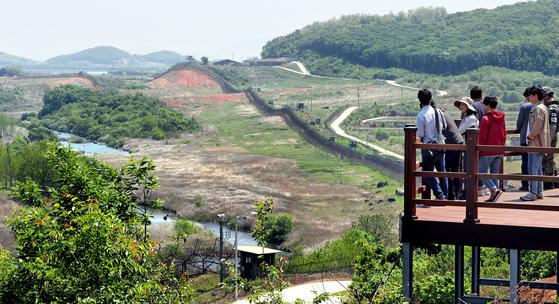 DMZ 평화의길 철원 구간, 공작새능선전망대에서 바라본 DMZ 풍광. 철책 너머로 사람 손길 닿지 않은 역곡천과 숲이 보인다. [중앙포토]