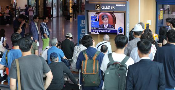 국정농단 사건 상고심 선고일인 29일 오후 서울 용산구 서울역에서 시민들이 대법원 선고 생중계를 보고 있다. 우상조 기자