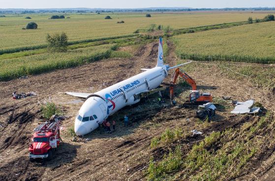 러시아 공사관계자들이 23일 불시착한 에어버스 여객기를 두산 굴착기로 분해하고 있다.[EPA=연합뉴스]