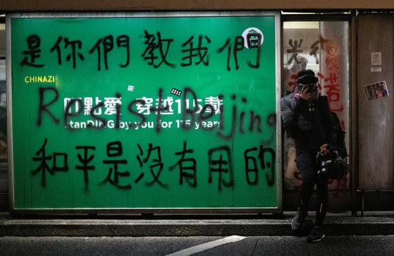 """지난달 31일 """"당신네가 우리에게 가르치지 않았나. 평화는 통하지 않는다는 걸"""" """"베이징에 저항하자"""" """"CHINAZI""""등의 문구가 적힌 반중국 표어 옆에서 시위에 참여한 한 사람이 쉬고 있다. [로이터=연합뉴스]"""