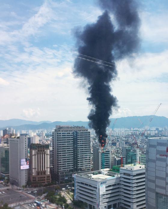 2일 오후 서울 송파구 방이동 송파구청 인근 빌딩 옥상에 불이나 검은 연기가 치솟고 있다. [독자 이성준 씨 촬영 제공=연합뉴스]
