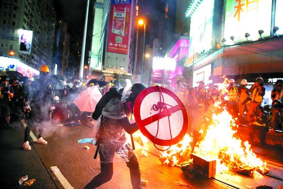 홍콩 경찰의 불허 결정에도 지난달 31일(현지시간) 열린 '범죄인 인도 법안' 반대 시위에서 경찰과 시위대가 또다시 충돌했다. 13주째 이어진 이번 집회에서 경찰은 과격 시위대 색출을 위해 파란색 염료가 들어간 물대포를 발사했고, 시위대는 화염병과 벽돌을 던지며 맞섰다. 집회에 참여한 한 시위대가 도로표지판을 방패 삼아 경찰과 대치하고 있다. 오늘(2일)도 홍콩 국제공항에서 연이은 시위와 총파업 등이 예고됐다. [AP=연합뉴스]