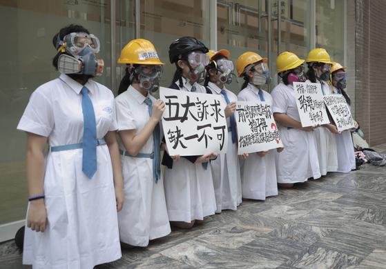 """방독면과 헬멧을 쓴 홍콩 성 프랜시스 캐노시안 고교 학생들이 2일(현지시간) """"5대 요구사항은 필수 불가결한 것""""이라고 쓴 플래카드를 들고 있다. [AP=연합뉴스]"""