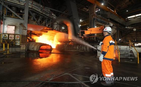 지난해 7월 전남 광양시 포스코 광양제철소 제5고로에서 한 근로자가 뜨거운 쇳물 곁에서 작업을 하고 있다. [연합뉴스]