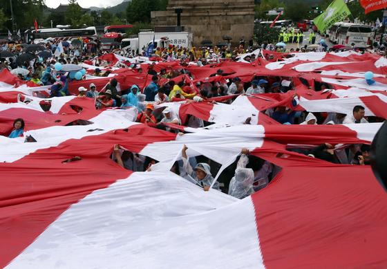 지난 8월 15일 8·15 전국 노동자 대회 참가자 등 일본 아베 정부를 규탄하는 시민들이 서울 종로구 일본대사관 앞에서 전범기인 욱일기를 찢는 퍼포먼스를 하고 있다. [연합뉴스]