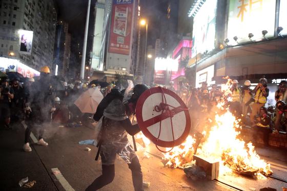 홍콩의 한 시위 참가자가 지난 8월 31일 방패를 들고 집기가 불타고 있는 거리에서 경찰과 대치하고 있다. [AP=연합뉴스]