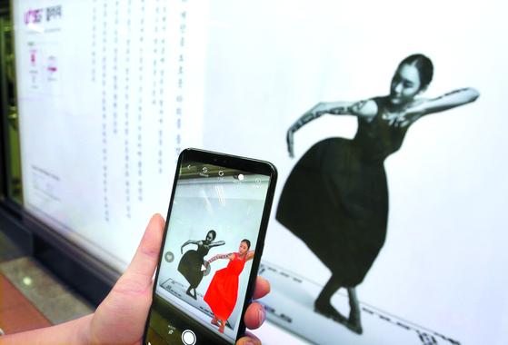 LG유플러스가 서울 지하철 6호선 공덕역에 꾸민 5G 기반 증강현실(AR) 갤러리에서 지하철을 기다리던 탑승객이 'U+ AR'로 무용가 김하나씨의 춤사위를 감상하고 있다. [사진 LG유플러스]