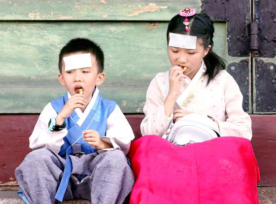 지난 10일 폭염이 기승을 부리는 한낮에 서울 종로구 경복궁을 찾은 외국인 어린이들이 이마에 쿨패치를 붙이고 있다. [뉴시스]