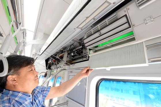 서울교통공사 관계자가 신형 전동차에서 객실 내에 설치된 공기질 개선 장치를 선보이고 있다. [뉴시스]