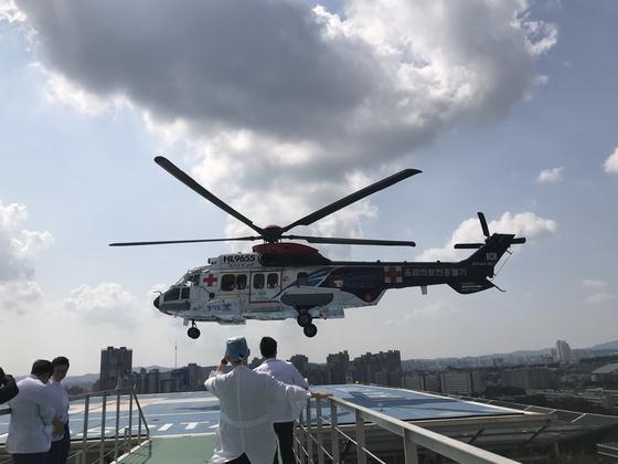 아주대 이국종 교수의 닥터헬기가 병원 옥상 착륙장에 내리고 있다. 사진 중앙의 모자를 쓴 사람이 이 교수다. [사진 아주대 권역외상센터]