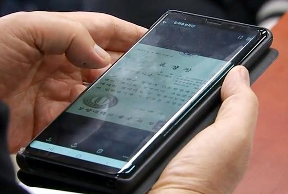 박지원 의원이 6일 인사청문회 도중 조국 법무부 장관 후보자 딸의 표창장 사진을 확인하고 있다.[사진 YTN 캡처]