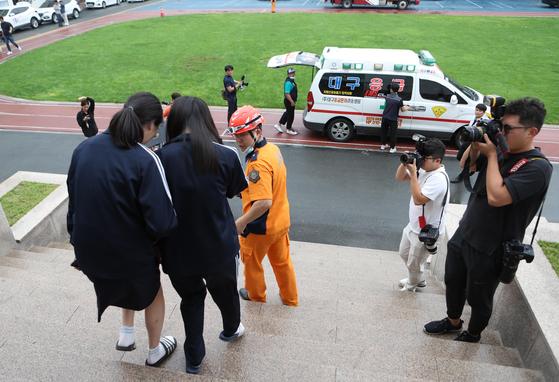 지난 2일 오후 대구시 북구 침산동 경상여자고등학교에서 악취를 맡고 이상증세를 보이는 학생들이 병원으로 이송되고 있다. [연합뉴스]