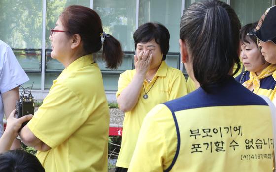 세월호 희생자 유가족들이 8월 25일 오후 송파구 서울동부지법에서 열린 '세월호 특조위 활동 방해'와 관련 직권남용권리행사방해 등 혐의에 대한 1심 선고공판을 마친 뒤 기자회견을 하며 눈물을 훔치고 있다. [뉴스1]