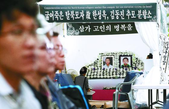 지난달 30일 서울 광화문 광장 앞에 마련된 탈북자 한모씨 모자의 추모 분향소 앞에서 관계자들이 시위를 벌이고 있다. [뉴스1]