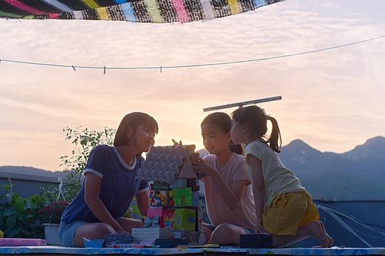 영화 '우리집'의 세 주인공(오른쪽부터). 하나와 유미, 유진 자매. 이들은 각자 집을 사수하기 위해 고군분투 한다. 사진은 유미가 주은 박스로 그들이 꿈꾸는 집을 만들고 있는 모습이다. [사진 아토ATO]