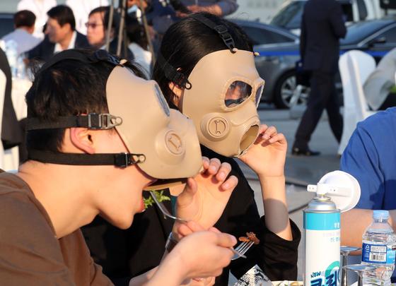 한반도평화에너지센터가 주최한 '미세먼지 속의 다이닝'행사가 14일 오후 서울광화문광장에서 열렸다. 참석자들이 미세먼지에 대한 경각심을 일깨우기 위해 마스크를 쓰고 식사하는 모습을 연출하고 있다. 변선구 기자.