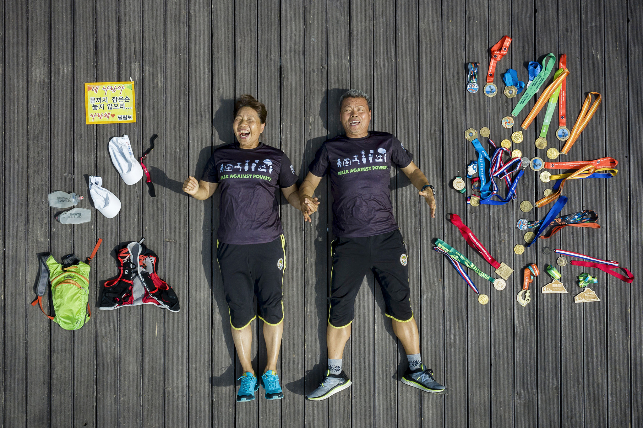 시각장애인으로 340여 회 마라톤 완주에 성공한 김미순씨와 두 손을 꼭 잡아 항상 그의 두 눈이 되어주는 남편 김효근씨. 왼쪽에는 마라톤에 사용하는 물품들이, 오른쪽에는 그간 완주로 받은 메달들이 자리했다. 장진영 기자