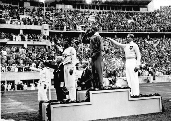 1936년 베를린 올림픽에서 육상 4관왕이 된 미국의 제시 오웬 선수(가운대)가 높이뛰기 시상식장에서 게양되는 성조기를 향해 거수경례를 하고 있다. 동메달을 딴 독일의 롱 선수와 대화 관계자들은 나치식 경례를 하고 있다. [독일 연방 문서보관소]