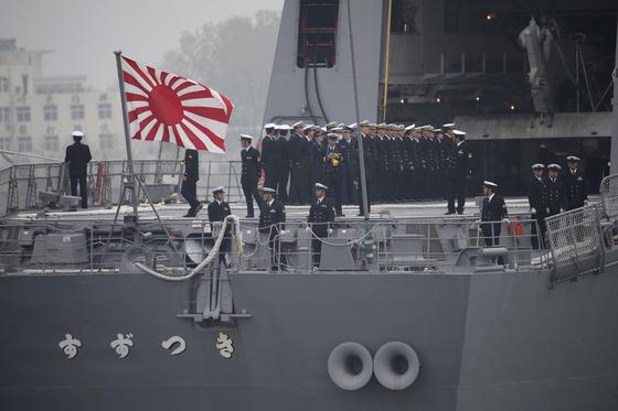 중국 인민해방군 해군 창설 70주년 기념 국제 관함식에 참가한 본 해상자위대 소속 스즈키 함이 중국 칭다오항에 입항한 모습.중국을 방문한 일본 함정으로는 처음 욱일기를 게양했다. 일본은 도켜 올림픽과 패럴림픽에 욱일기를 이용한 응원을 막지 않을 방침이다. 평화와 하합의 제전인 올림픽에서 군대가 쓰는 군기를 흔들며 응원하는 나라를 정상 국가로 보기는 어려울 것이다. [EPA]