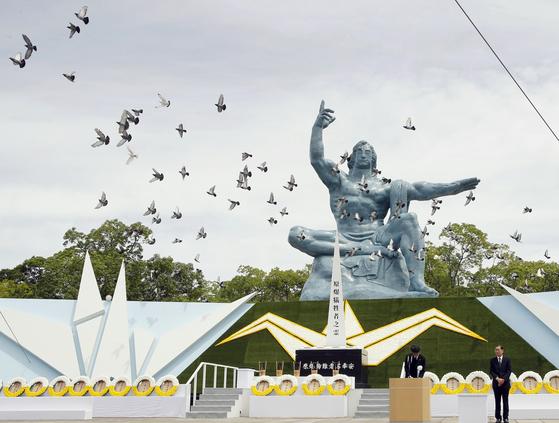 1945년 8월 9일 나가사키 원자폭탄 투하 현장에 설치된 평화공원에서 비둘기들이 조형물 앞을 날아가고 있다. 내년 열릴 도쿄 여름 올림픽은 하필이면 나가사키에 원자폭탄이 투하된 8월 9일을 폐막일로 잡았다. 폭염이 계속되는 계절이기도 하다. [AP=연합뉴스]