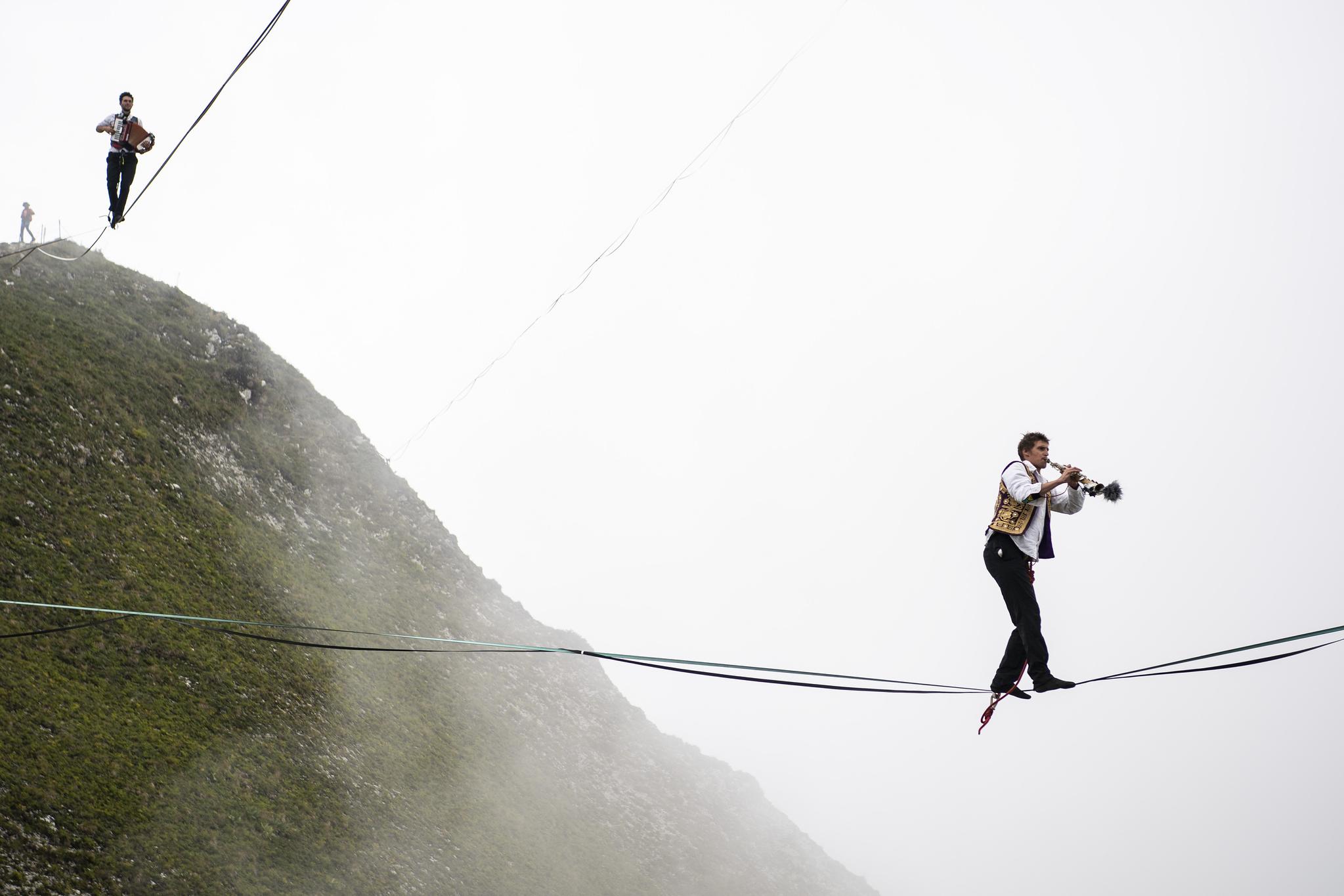 한 참가자가 7일(현지시간) 스위스 그뤼에르 인근 해발 2000m 상공의 알프스 산맥 봉우리에 연결된 외줄을 타고 건너며 트럼펫을 연주하고 있다. [AP=연합뉴스]