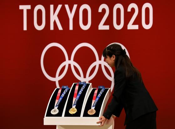 도쿄올림픽·패럴림픽을 1년 앞둔 지난 7월 24일 도쿄에서 열린 행사장에서 금, 은, 동메달을 공개하고 있다. 2020년 도쿄 올림픽 패럴림픽이 과거사를 묻고 일본을 전쟁 할 수 있는 나라로 만들려는 아베 퐁리의 정치적 행사로 변질될 수 있다는 우려가 나오고 있다. [EPA=연합뉴스]