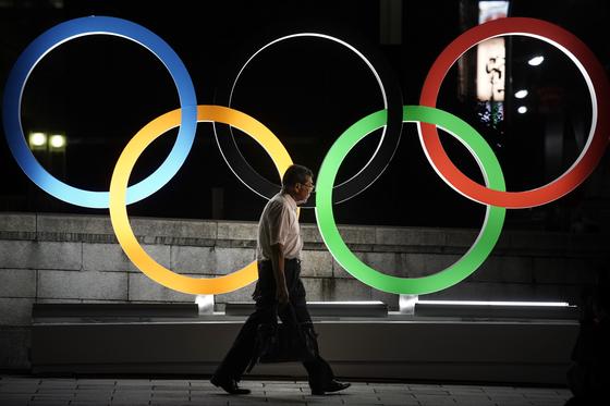 도쿄 올림픽 패럴림픽 개최 1년을 앞둔 지난 7월 23일 도쿄 시내에 설치된 올림픽 앰블렘 앞을 한 남자가 지나가고 있다. [AP=연합뉴스]