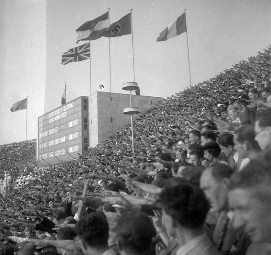 1936년 베를린 올림픽 당시 스타디움에 나치 깃발이 휘날리는 가운데 관객들이 나치식 경례를 하고 있다. 평화와 하합의 장이 돼야 할 올림픽이 나치 이념과 게르만족 우월주의의 선전장으로 변질된 나쁜 선례다. [위키피디아]