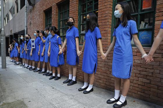 홍콩의 중고등학생들이 9일 손을 잡고 '인간 띠'를 만드는 시위를 하고 있다. [AP=연합뉴스]