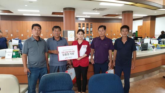 민족 고유 명절 추석을 앞두고 강원도 고성군 산불피해 마을 대표에게 상품권을 전달한 후 기념촬영을 하고 있다.