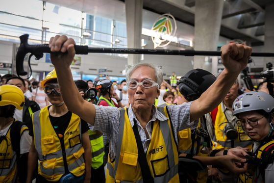 85세 웡 할아버지가 7일(현지시간) 홍콩 퉁충 지역에서 '실버헤어' 자원봉사자들과 함께 자신의 지팡이를 머리 위로 들어 경찰들로 부터 시위대를 보호하고 있다. [AFP=연합뉴스]