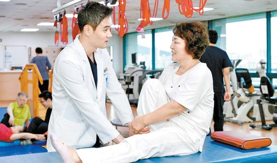 분당 서울나우병원 류호광 원장(왼쪽)이 무릎 인공관절 수술 후 다리 근력을 강화하는 환자의 재활치료를 살펴보고 있다. 프리랜서 김동하