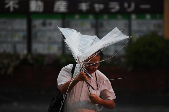 9일(현지시간) 일본 도쿄의 한 시민이 바람을 맞으며 아침 출근을 서두르고 있다. [AFP=연합뉴스}