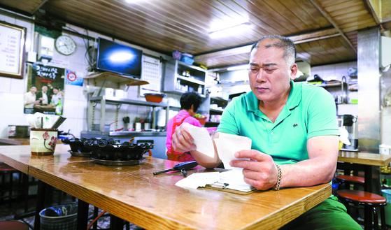 서울 종로에서 식당 '왕벌집'을 운영하는 이근재씨가 전표를 보고 있다. 임현동 기자