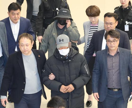 '빚투' 논란을 촉발한 마이크로닷 부모가 지난 4월 인천국제공항을 통해 귀국한 뒤 경찰에 체포돼 공항을 빠져나가고 있다. [연합뉴스]